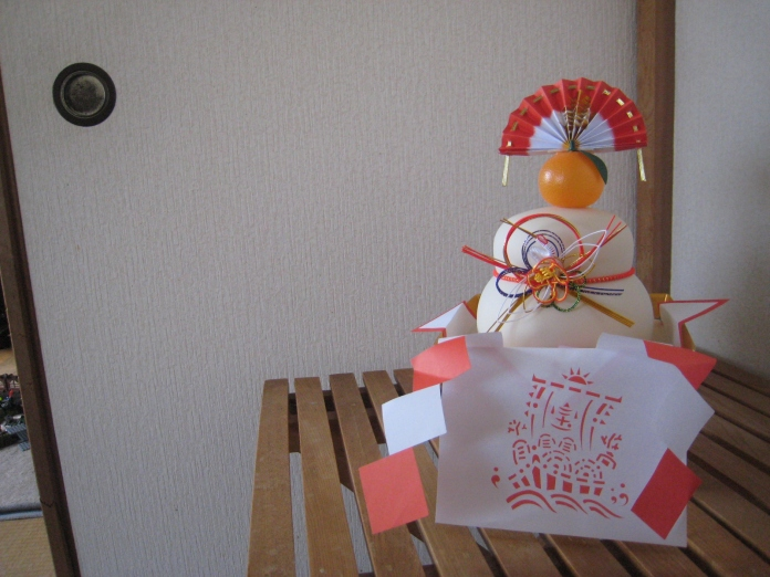 Traditional Japanese New Year decoration in front of hated paper doors.